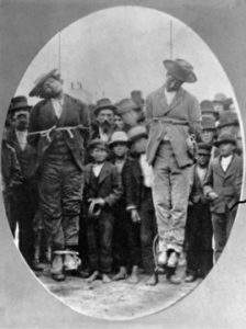 """Foto tomada del libro """"Forgotten Dead"""". En la imagen, un par de hombres descendientes de mexicanos son observados por la multitud después de ser linchados en la localidad de Santa Cruz, California."""